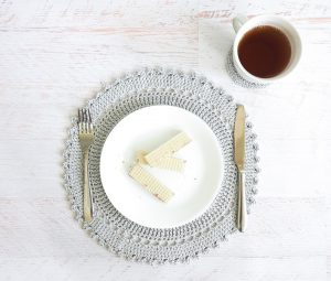 The Table Placement Set includes an intricate crocheted placemat and coaster pattern. These delicate, lacy pieces are the perfect accent to that impressive feast you just prepared. #crochetpattern #crochetplacemat #crochetcoasters #crochetlove #crochetaddict