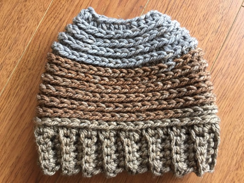 At the Woods Messy Bun Hat - These crochet hat patterns are so stylish and fun to make. Each one uses different crochet stitches to create one of a kind designs. #MessyBunHatCrochetPatterns #HatCrochetPatterns #CrochetPatterns