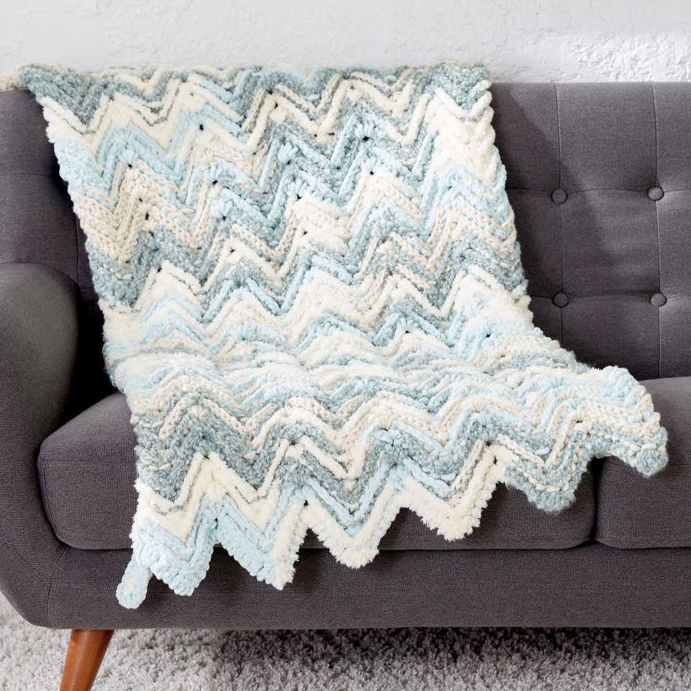 Bernat Raised Chevron Afghan - These crochet blankets are so pretty and an adventure to make. Test out your stitch knowledge with these exciting afghan patterns. #ChevronCrochetBlanket #CrochetBlanket #CrochetPatterns