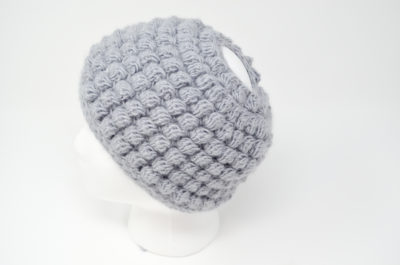 Bobble Messy Bun Hat - These crochet hat patterns are so stylish and fun to make. Each one uses different crochet stitches to create one of a kind designs. #MessyBunHatCrochetPatterns #HatCrochetPatterns #CrochetPatterns