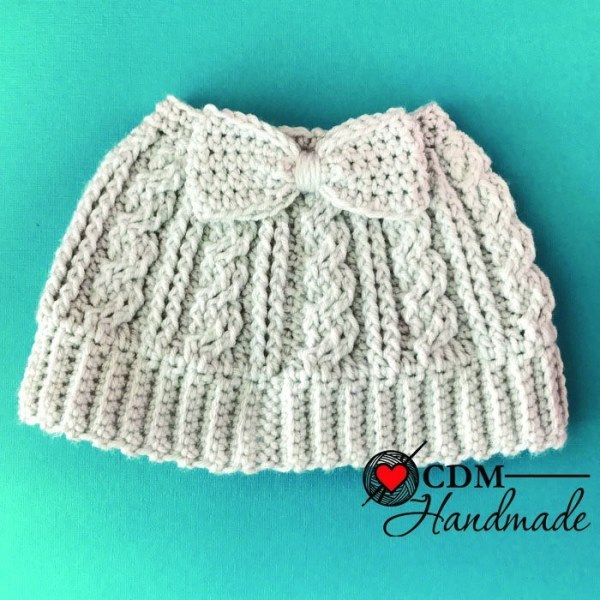 Cabled Messy Bun Bow Hat - These crochet hat patterns are so stylish and fun to make. Each one uses different crochet stitches to create one of a kind designs. #MessyBunHatCrochetPatterns #HatCrochetPatterns #CrochetPatterns