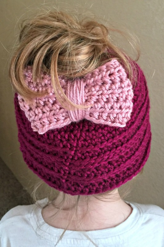 Messy Bun Hat with Adjustable Bow - These crochet hat patterns are so stylish and fun to make. Each one uses different crochet stitches to create one of a kind designs. #MessyBunHatCrochetPatterns #HatCrochetPatterns #CrochetPatterns